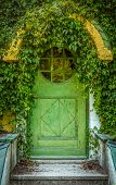 stock photo of creeper  - Green Door Of Fairytale Cottage With Round Window - JPG