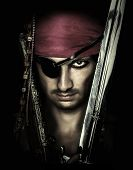 stock photo of sword  - Portrait of handsome male pirate holding sword on black background - JPG