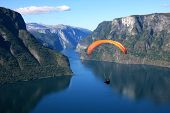 stock photo of hang-gliding  - Paraglider flies through the nice Norwegian fjord - JPG