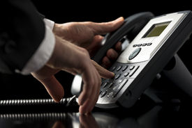 stock photo of keypad  - Low angle closeup view of the hands of a businessman in a suit dialing out on a telephone call using a dial - JPG