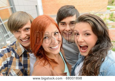 Cheerful teenager friends taking selfie having fun outside campus