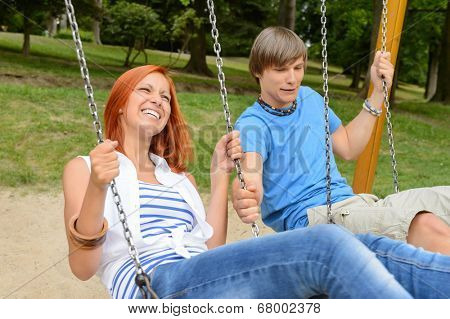 Cheerful teenage couple on swing in park girl laughing