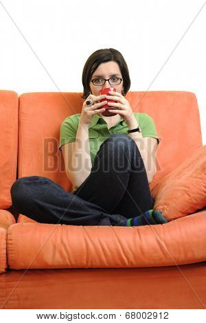 young woman isolated on white with cup off coffee talking and chating isolated on whtie on orange sofa