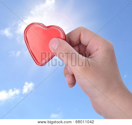 Children hand holding a heart-shaped candy