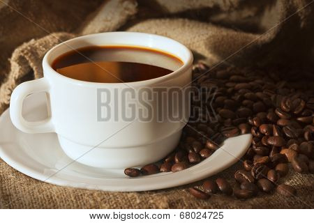 White Cup Of Coffee On Sacking And Coffee Beans