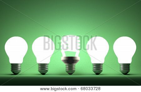 Glowing Spiral Light Bulb In Row Of Tungsten Ones On Green