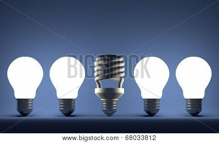 Dead Spiral Light Bulb In Row Of Glowing Tungsten Ones On Blue