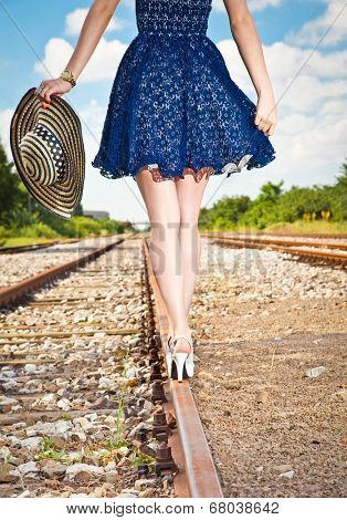 Beautiful woman with hat walking over railroad