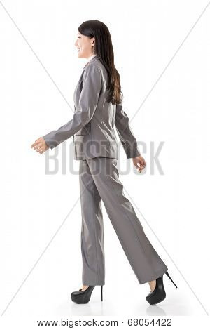 Full length portrait of Asian business woman walk, side view isolated on white background.