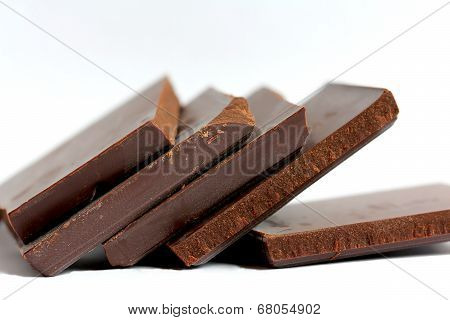 Close Up Of Cut Chocolate Pieces On White Background
