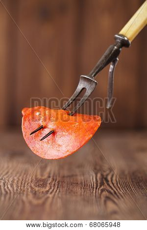 slice of sausage chorizo on meat fork and wooden backdrop