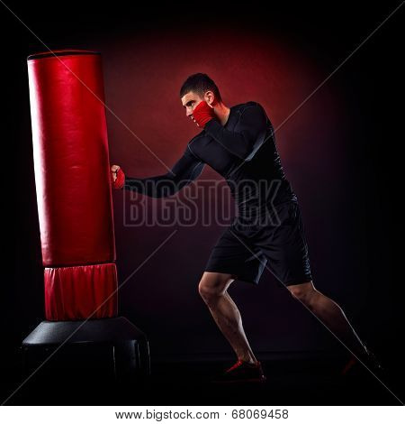 young man exercising bag boxing in studio