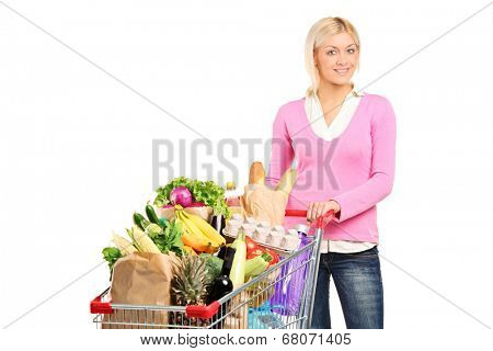 Woman pushing a shopping cart full of groceries isolated on white background