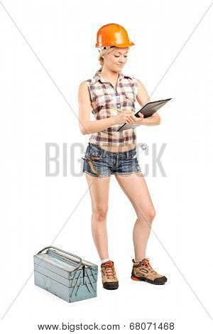 Full length portrait of a female mechanic writing on a clipboard isolated on white background