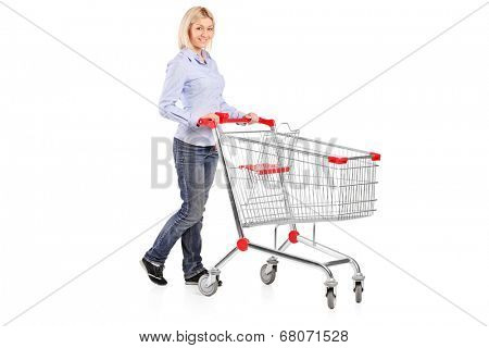 Full length portrait of a woman pushing a shopping trolley isolated on white background