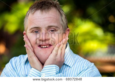 Handicapped  Boy With Hands On Face.