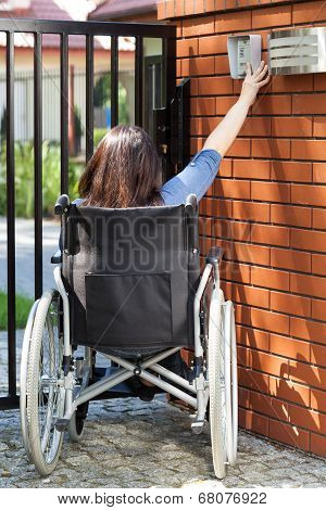 Woman On Wheelchair Dialing Intercom