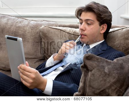 Young Man Relaxing With An E-cigarette