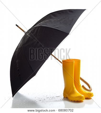 A pair of yellow rain boots and a black umbrella on a white background