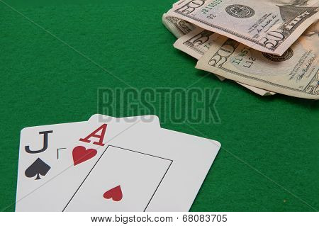 Blackjack hand with Dollar notes on green background