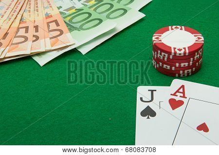Blackjack hand with Euro notes and chips on green background