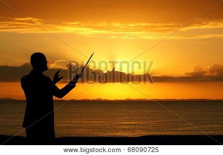 Man conducting people during a sunset at the beach