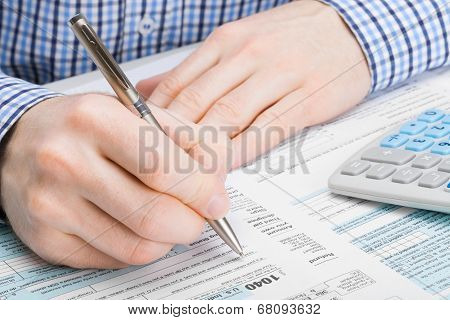 Male Filling Out 1040 United States Of America Tax Form - Studio Shot