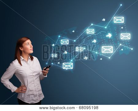 Attractive young lady standing and holding a phone with arrows and message icons
