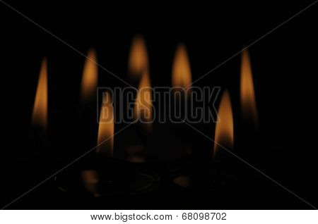 Group of several candle flames isolated over black background