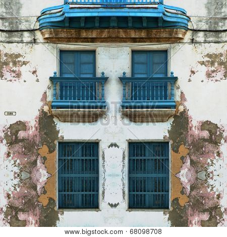 Detail of eroded Old Havana facade with blue windows