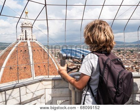 Boy looking through a sightseeing binoculars the Dome of Basilica di Santa Maria del Fiore (Saint Mary of the Flower), Florence, Tuscany, Italy, Europe.
