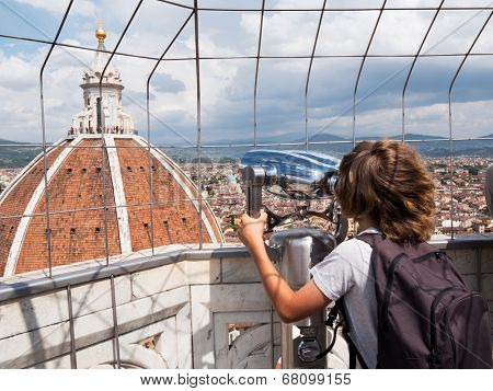 Tourism concept: boy looking through a sightseeing binoculars the Dome of Basilica di Santa Maria del Fiore (Saint Mary of the Flower), Florence, Tuscany, Italy, Europe.