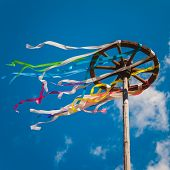 foto of wind wheel  - Wooden wheel with bright ribbons on blue sky background - JPG