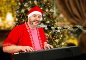 stock photo of christmas song  - Huge mature man in Santa Claus costume singing Christmas songs - JPG