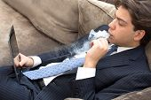 pic of exhale  - Businessman relaxing on a sofa smoking and working puffing on an electronic cigarette or e - JPG