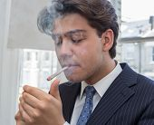 foto of cigarette lighter  - Young businessman lighting up a cigarette with a lighter in his cupped hands puffing smoke while standing in an urban office with windows - JPG