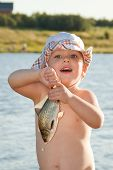 stock photo of panama hat  - Little boy in panama hat holding a fish is on the bank of a pond - JPG