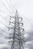 stock photo of transmission lines  - a high voltage transmission line tower against blue sky - JPG
