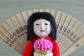 stock photo of geisha  - Japanese geisha doll with dark hair in a dress - JPG