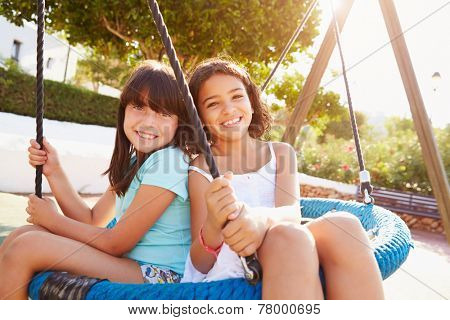 Two Girls Having Fun On Swing In Playground