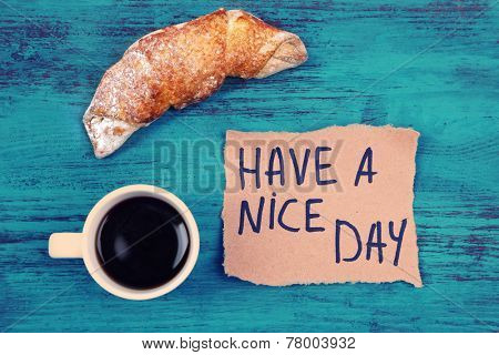Composition of coffee, fresh croissant and paper card on wooden background