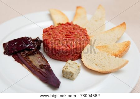 Tartare with toasts and chicory cooked in wine in plate