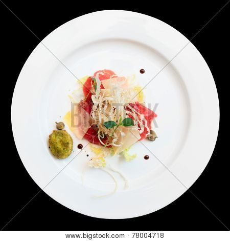 Tuna carpaccio on plate isolated over black background