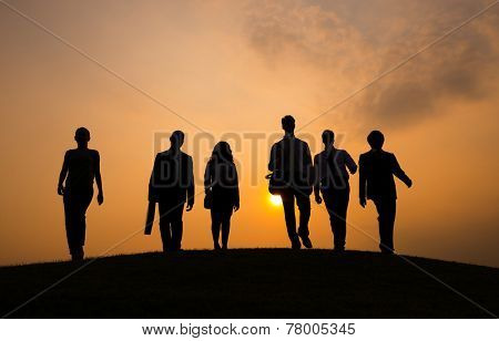 Business People Walking on the Hill Under Sunset