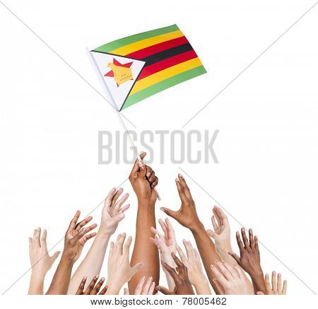Group of multi-ethnic people reaching for and holding the flag of Zimbabwe.