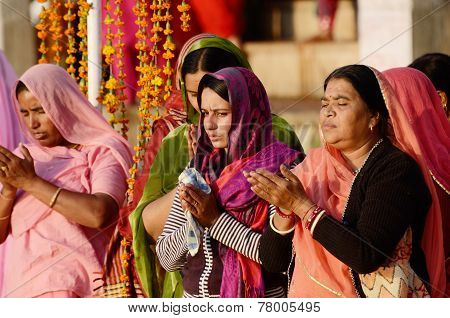 Senior and young hindu women in colourful sari perform puja during sunset at holy Sarovar lake,India