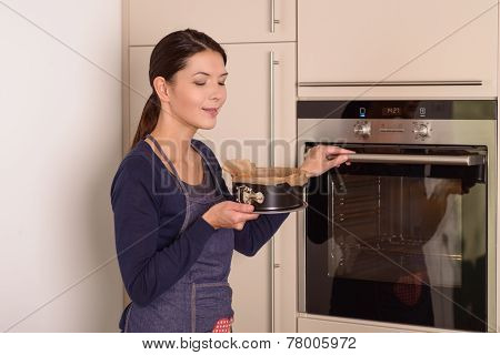Young Woman Placing A Cake In The Oven