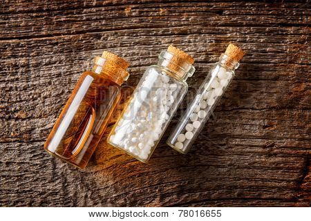 Homeopathic lactose sugar globules and fluid in glass bottles