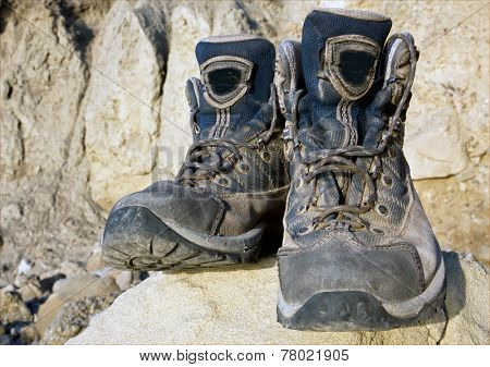 Tourists boots on stone in mountains