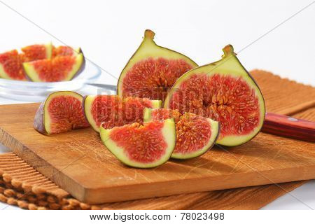 sweet figs halved with sharp knife, served on the wooden cutting board